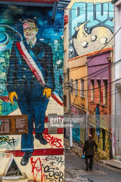 Street mural of former President Salvador Allende, with old man walking down the adjacent sidestreet, Valparaiso, UNESCO World Heritage Site, Chile