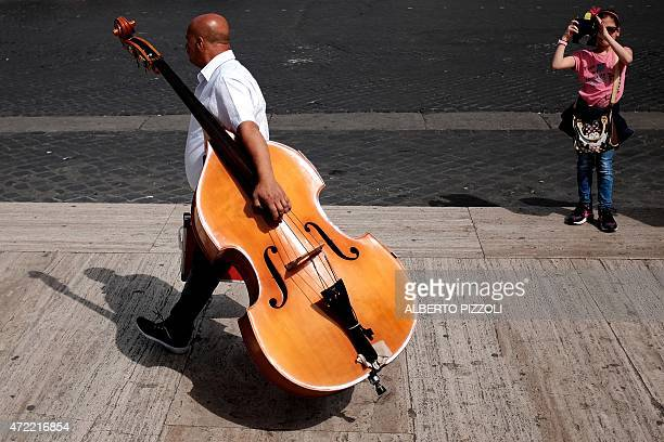 A street musician carries a contrabass as a little girl takes a pictures with a mobile phone on May 5 2015 in Rome AFP PHOTO / ALBERTO PIZZOLI