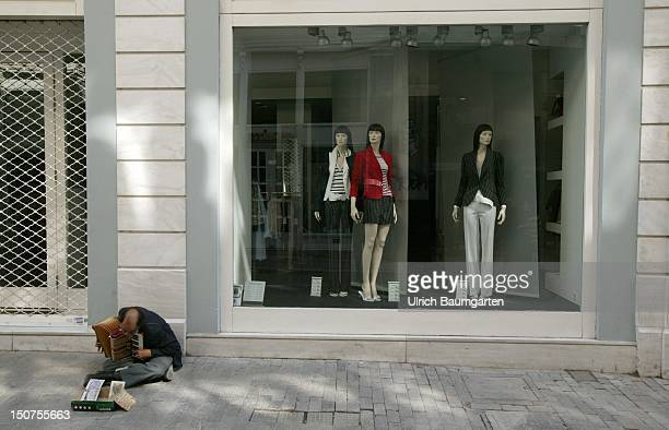 Street musician in fromt of a fashion boutique in the centre of Athens