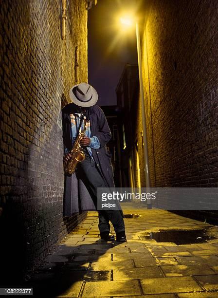 Straßenmusiker spielen Saxophon in alley
