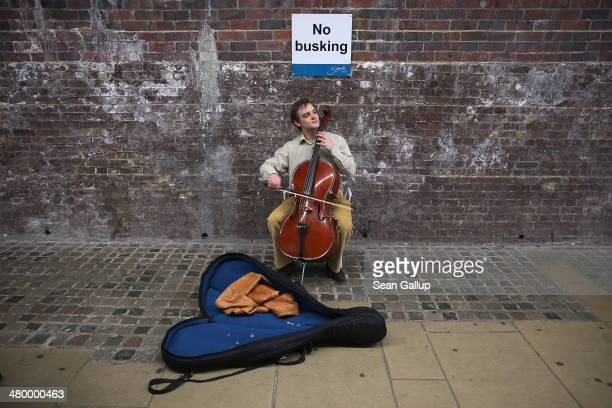 A street musician plays a cello under a sign that explicitly forbids busking under a bridge near the Thames River on March 21 2014 in London United...