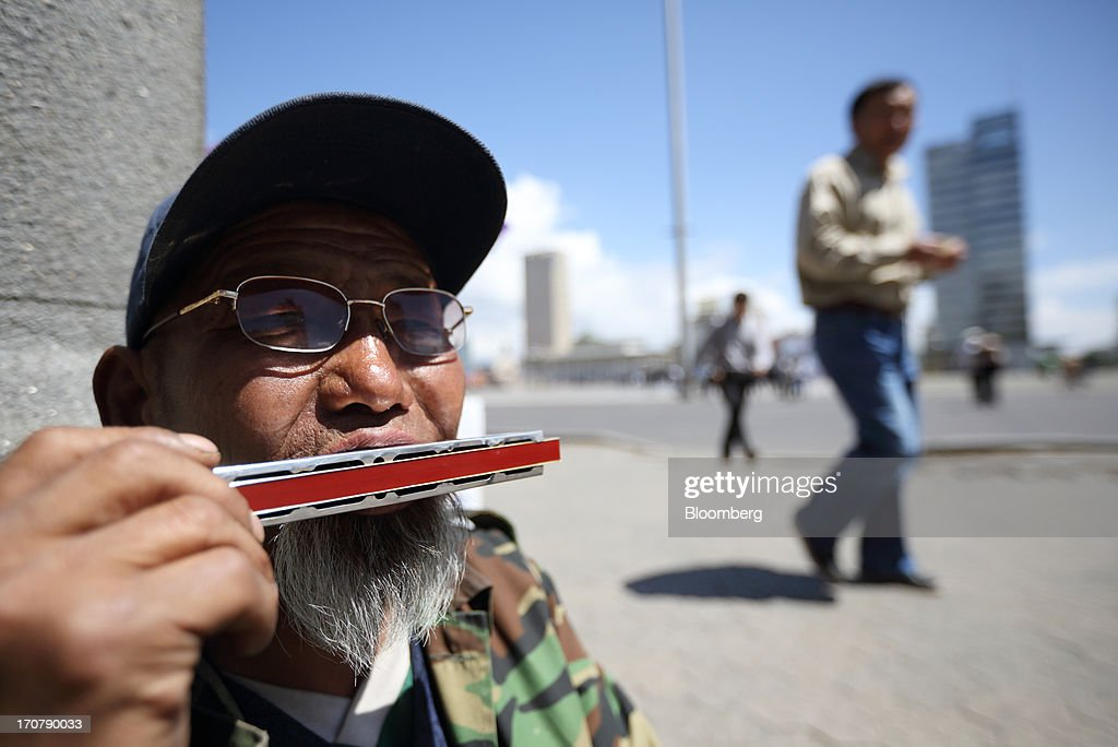 A street musician plays a mouth organ outside the Mongolian Stock Exchange in Ulaanbaatar, Mongolia, on Thursday, June 13, 2013. Mongolia, a country of almost 2.9 million people, is experiencing double-digit growth and new opportunities in the mining industry. Photographer: Tomohiro Ohsumi/Bloomberg via Getty Images