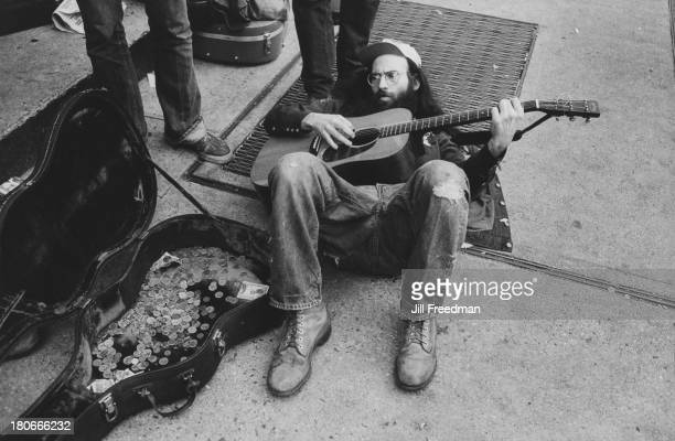 A street musician plays guitar lying on his back Greenwich Village New York City circa 1994