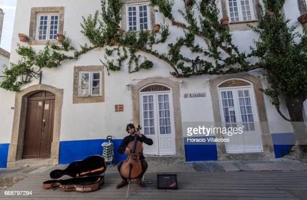 A street musician plays his cello in Rua Direita during Good Friday when the town receives many tourists attracted for Holy Week religious activities...