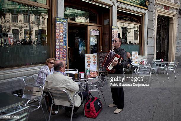 A street musician plays the accordion for money at a cafe terrace on October 11 2012 in Madrid Spain Ratings agency Standard Poor's has cut Spain's...