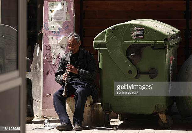 A street musician plays the clarinette next to a garbage wheelie bin on Nicosia's central Ledra street on March 20 2013 Cypriot Finance Minister...
