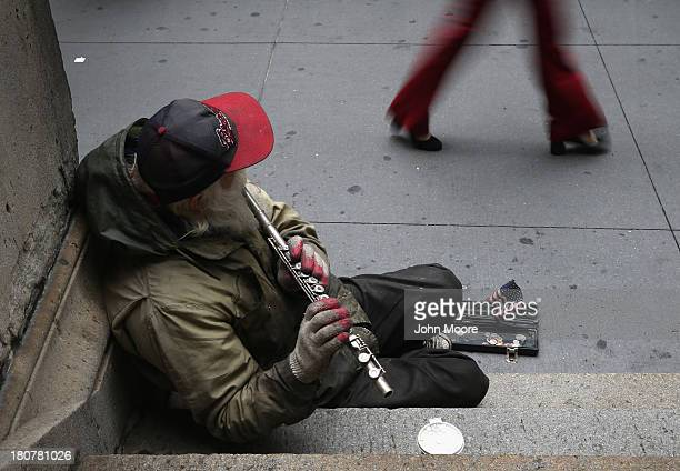 A street musician plays 'Yankee Doodle' as pedestrians pass by outside the New York Stock Exchange on Wall Street on September 16 2013 in New York...