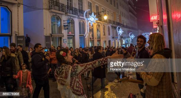 Street musicians entertain the crowd of tourists and shoppers under Christmas and New Year light displays in Rua do Carmo on December 9 2017 in...