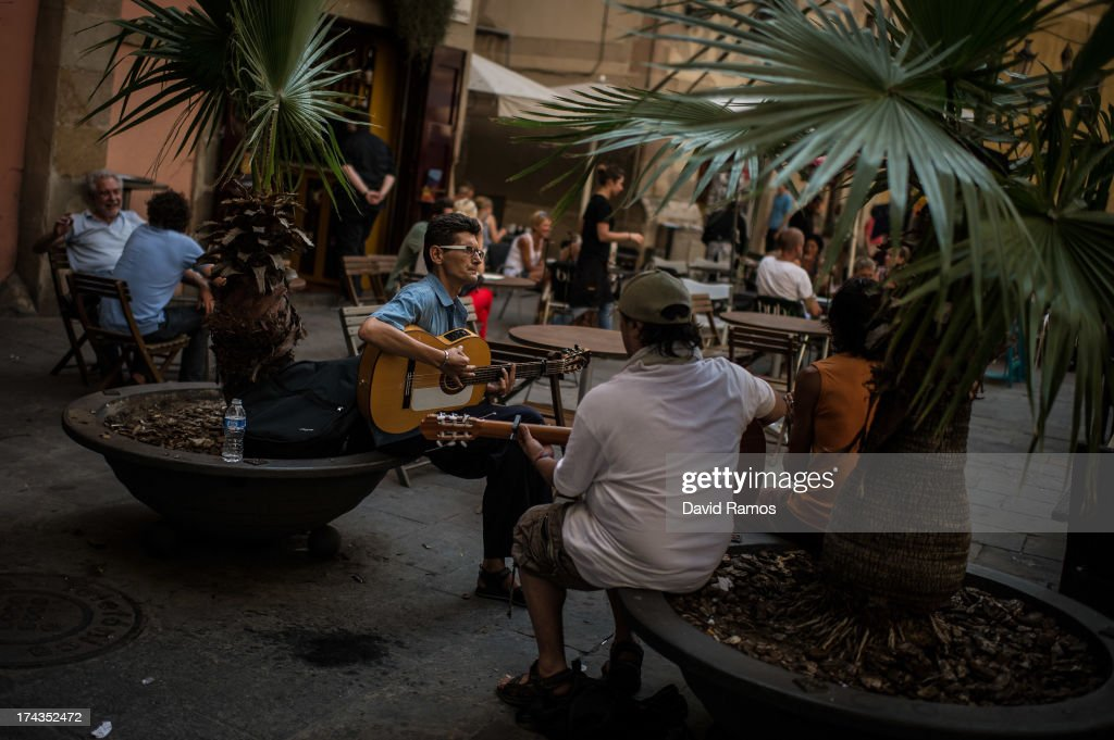 Street musicians play next to a bar terrace on July 24, 2013 in Barcelona, Spain. Foreign visitors to Spain set a new record high in June surpassing six million tourists for the first time ever and climbing by 5.3 percent since June 2012.Ê