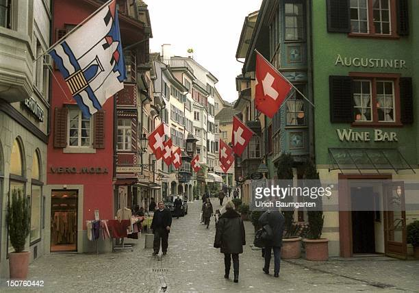 Street of the old part of the town with Swiss flags in Zurich