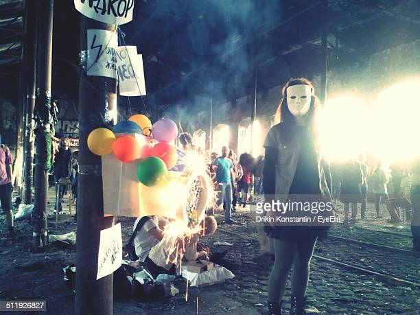 Street party scene with girl wearing mask
