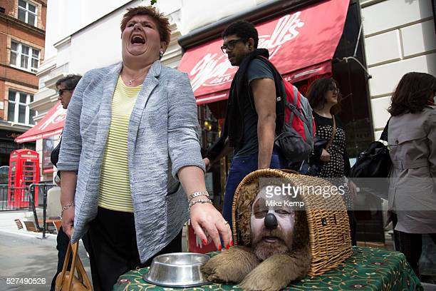 Street performer acts as a humourous dog Collecting money whilst making fun and talking to his audience Covent Garden in the West End of London This...