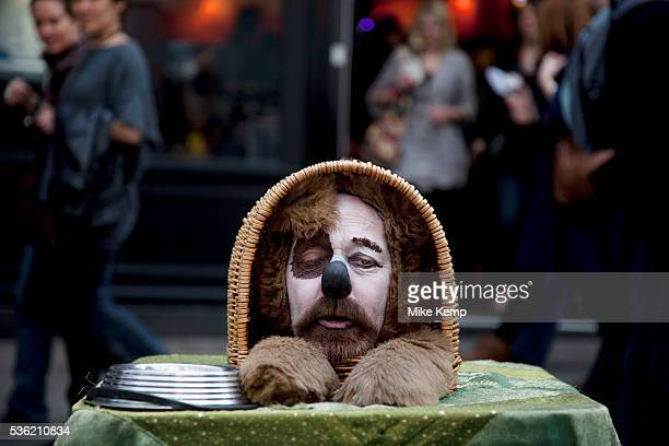 Street performer acts as a humourous dog Collecting money whilst making fun and talking to his audience Covent Garden in the West End of London