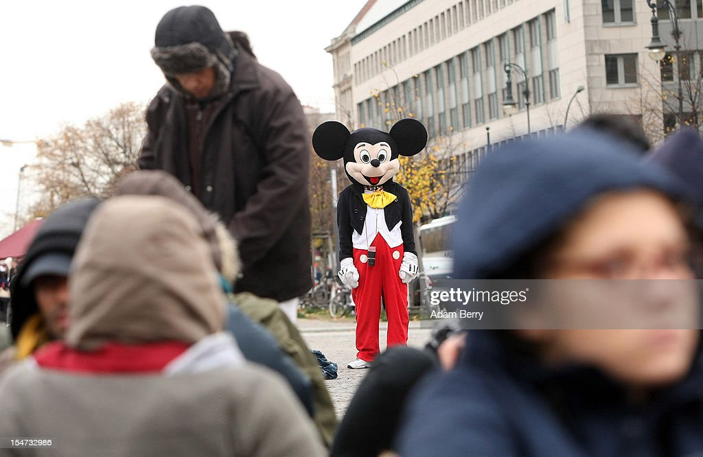 A street performer dressed as Mickey Mouse stands near protesting refugees as they stage a hunger strike in front of the Brandenburg Gate on October 25, 2012 in Berlin, Germany. The demonstrators, predominantly from Iran, Afghanistan and Iraq are subsisting on only water, tea and coffee without sugar, and claim to have been told by the police that they are not allowed blankets or tents. They have been sitting in front of the Brandenburg Gate since last night, and say they will continue their strike until the German government responds to their demands for a halt to deportations and faster processing of asylum applications.