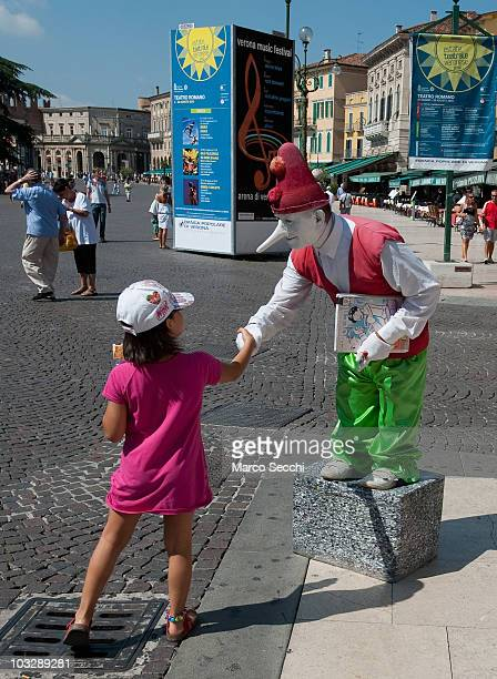A street performer dressed as Pinocchio shake hands with a little girl in Piazza Bra outside the Arena on August 8 2010 in Verona Italy The city of...