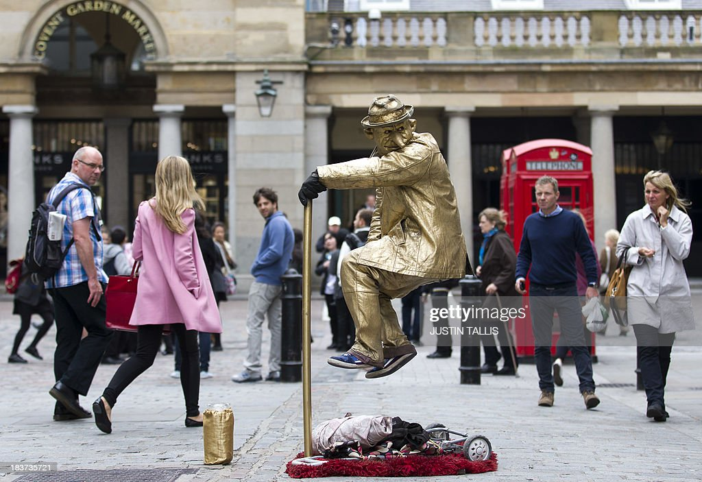 A street performer dressed in a gold costume looks on in Covent Garden in London, on October 9, 2013. World famous Covent Garden is one of the few areas of London licensed for street performers.