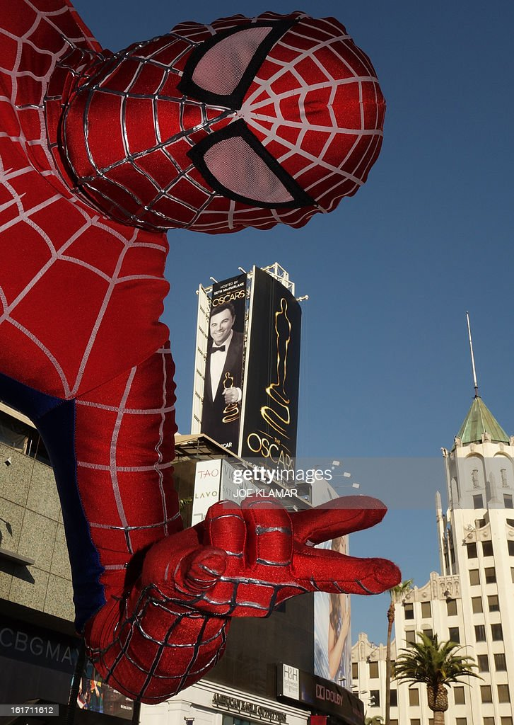 A street performer garbed as Spiderman strikes a pose backed by the first billboard announcing this year's upcoming OSCARS, the 85th Academy Awards, in front of the Dolby Theatre in Hollywood, California, on February 14, 2013. The ceremony is scheduled for February 24, 2013. AFP PHOTO/JOE KLAMAR