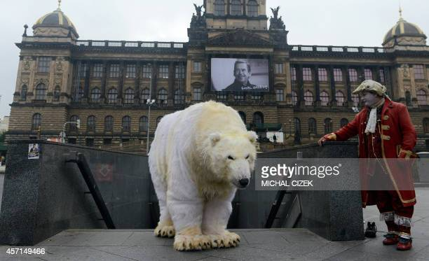 A street performer looks on as a Greenpeace activist dressed like a polar bear poses in front of the National Theatre on October 13 2014 in Prague...