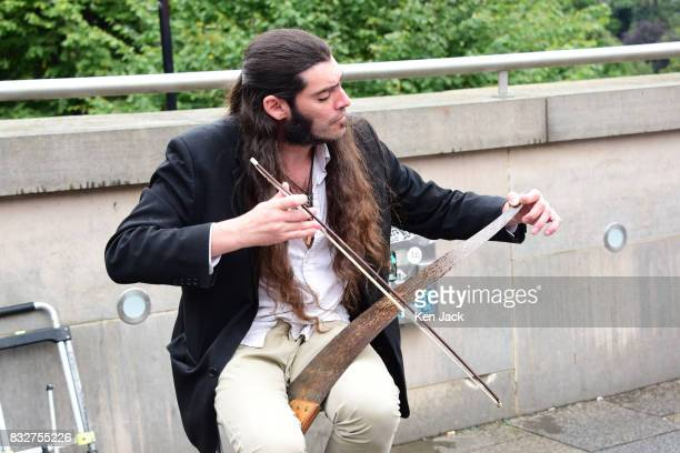 A street performer plays a saw during the Edinburgh Festival Fringe on August 16 2017 in Edinburgh Scotland The Fringe is celebrating its 70th year...