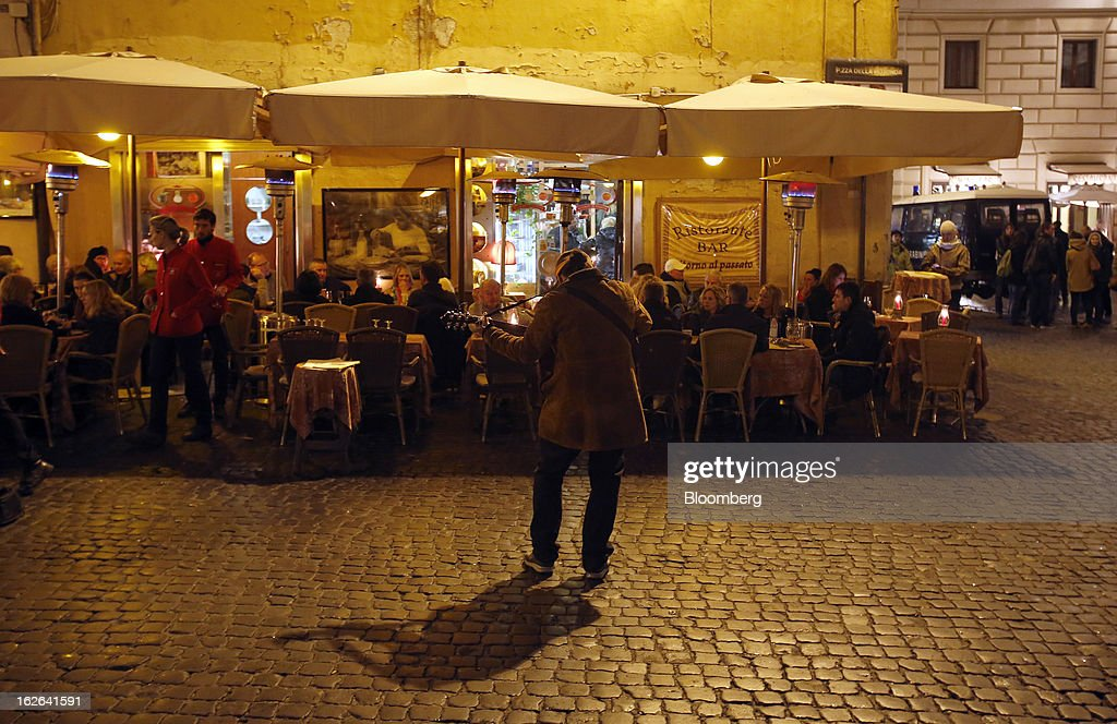 A street performer plays his guitar as customers sit outside a restaurant at night in downtown Rome, Italy, on Friday, Feb. 22, 2013. Italy's borrowing costs rose at an auction of zero-coupon bonds today as investors await the outcome of an election that may produce a fragmented parliament. Photographer: Alessia Pierdomenico/Bloomberg via Getty Images