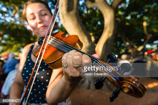A street performer plays the fiddle for visitors at an open-air market.