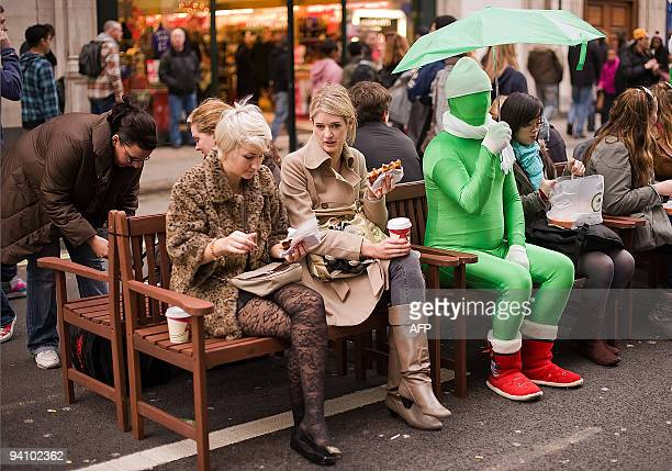 A street performer sits among the shoppers on Oxford Street in central London as the area is pedestrianised for a day to encourage people to come to...