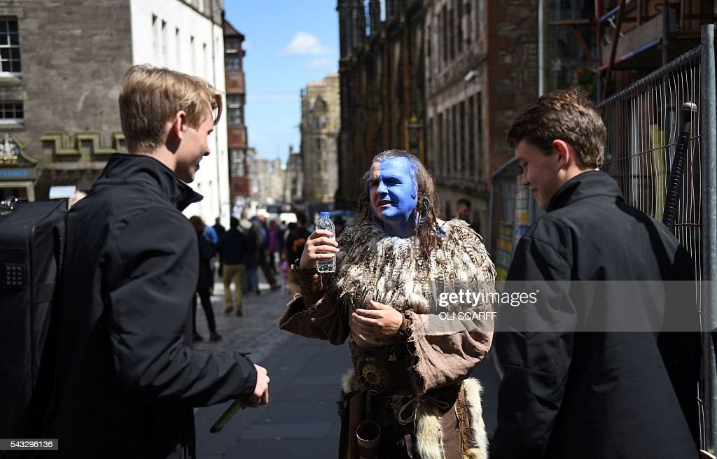 A street performer with a painted face and dressed in period costume speaks with holidaymakers in the city centre of Edinburgh, Scotland on June 27, 2016. Britain's historic decision to leave the 28-nation bloc has sent shockwaves through the political and economic fabric of the nation. It has also fuelled fears of a break-up of the United Kingdom with Scotland eyeing a new independence poll, and created turmoil in the opposition Labour party where leader Jeremy Corbyn is battling an all-out revolt. SCARFF