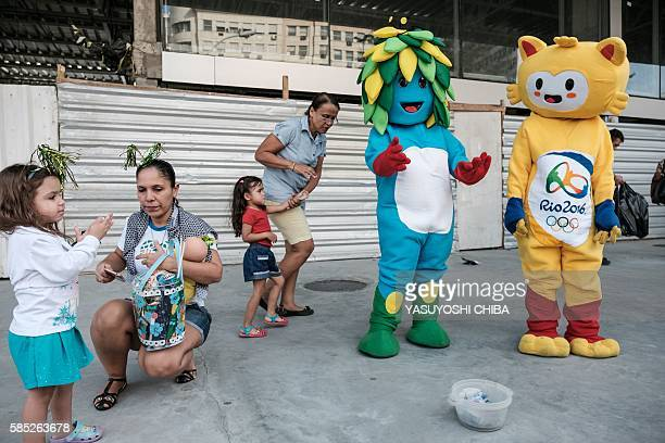 Street performers dressed as Rio 2016 Olympic Games mascot Vinicius and Rio 2016 Paralympic Games mascot Tom wait to take pictures with a family...