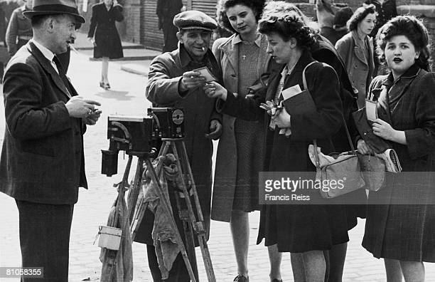 A street photographer shows some of his work to clients London 27th March 1946 The photographer is using a 1930's Aptus ferrotype camera with a...