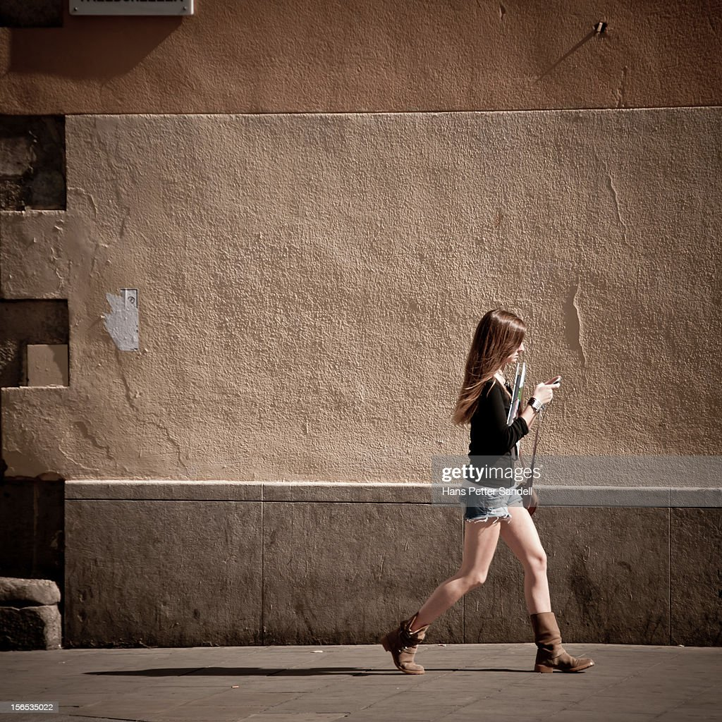 Street photography, woman walking while giving attention to her cell/mobile phone.