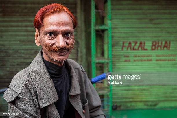 Street portrait of a man with red hair and mustache tinted with henna in Chandni chowk area of old Delhi India