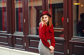 Street portrait of young beautiful happy smiling woman wearing stylish classic clothes. Model looking aside. Female fashion concept. Copy space, free text. Toned.