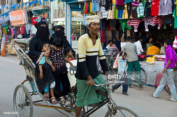 Street scene in holy city of Varanasi young muslim women in black burkhas ride with their children in rickshaw Benares Northern India