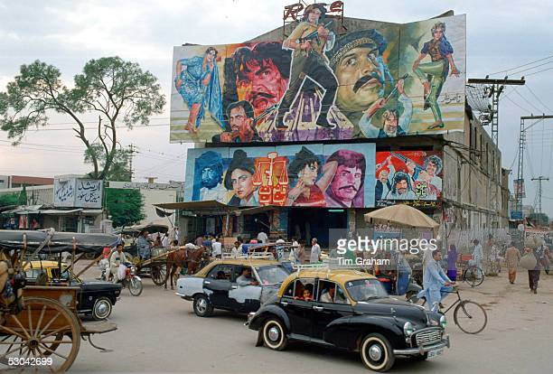 Street scene in Islamabad Pakistan showing rickshaws an old twotone Morris Minor car and the local cinema advertising films often described as...