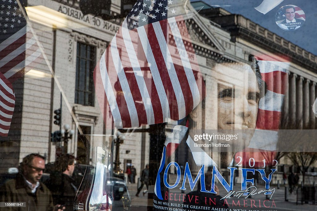 A street scene is reflected in the window of a gift shop near the White House on November 6, 2012 in Washington, DC. As Americans go to vote, recent polls show that President Barack Obama and Republican presidential candidate former Massachusetts Gov. Mitt Romney are in a virtual tie in the national polls.