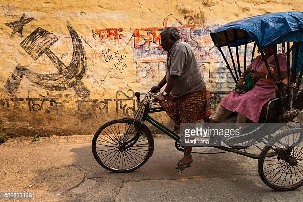 Street scene of a cycle rickshaw in a street near Kalighat Calcutta West Bengal India Symbol on the wall the Communist Party of India abbreviated CPI...