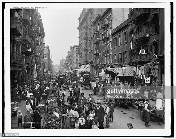 Street scene showing pedestrians shoppers and merchants with their vendor carts and stalls on Mulberry Street New York circa 1900