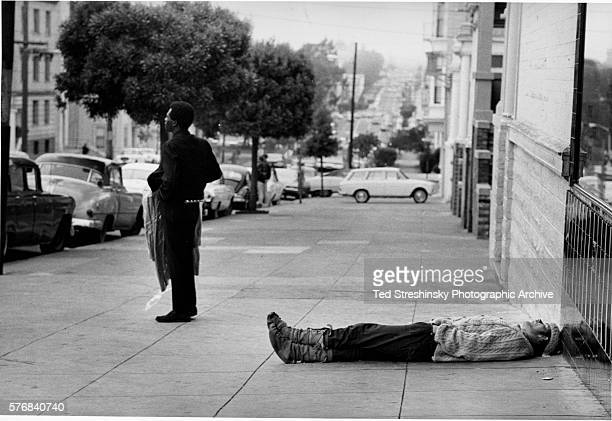 Street Scene With Man Sleeping on Sidewalk