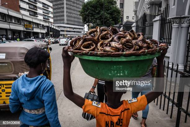 A street seller carries a basket of fish along a sidewalk in Lagos Nigeria on Wednesday July 26 2017 Nigeria's economy which in 2016 suffered its...