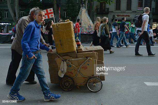 A street sellers push their trolley with some cold drinks inside the boxed on the main street in Tbilisi as many people of all age gathered in...