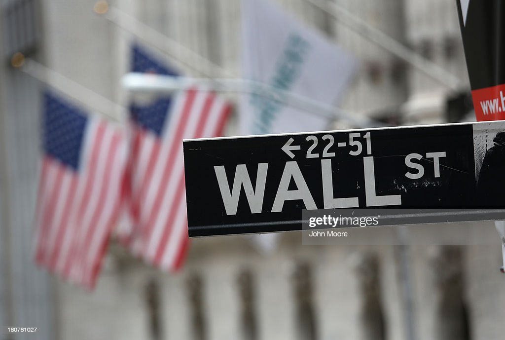A street sign for Wall Street hangs outside the New York Stock Exchange on September 16, 2013 in New York City. Five years after the beginning of the financlial crisis marked by the bankrupcy of Lehman Brothers, Wall Street has more than recovered its losses, although unemployment in the United States remains high.
