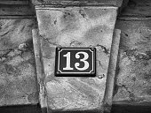 Old-fashioned enamel sign with house number 13. Sandstone facade of a medieval house. Franconia, Bavaria, Germany. Black & White with hard contrasts. Thirteen is a natural number and a prime number. I