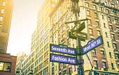 Street sign of Seventh and Fashion Ave with West 36th St at sunset in New York City - Urban concept and road direction in Manhattan - American world famous capital destination on warm vintage filter