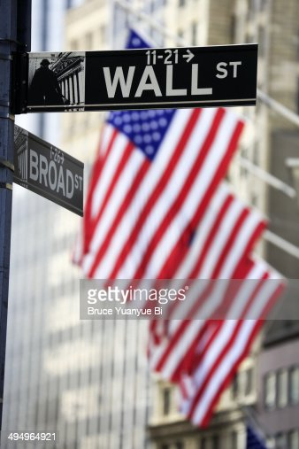 Street sign of Wall Street with American flags