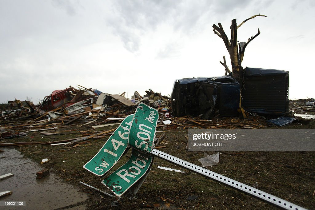 A street sign sits on the corner of Robinson Avenue and South West 146th Street on May 21, 2013 in Moore, Oklahoma. Families returned to a blasted moonscape that had been an American suburb Tuesday after a monstrous tornado tore through the outskirts of Oklahoma City, killing at least 24 people. Nine children were among the dead and entire neighborhoods vanished, with often the foundations being the only thing left of what used to be houses and cars tossed like toys and heaped in big piles. AFP PHOTO/Joshua LOTT