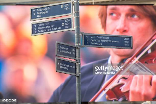 A street sign stands before a large screen showing a musician in a free openair performance of Beethoven's 9th Symphony and 'The Ode To Joy' at...