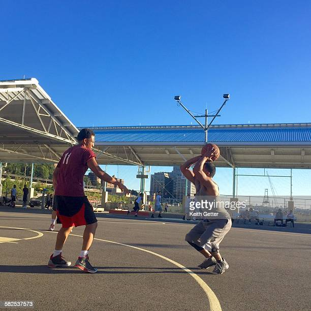 Basketball Players in Action playing a pickup game on an outside court under a blue sky in Brooklyn NYC