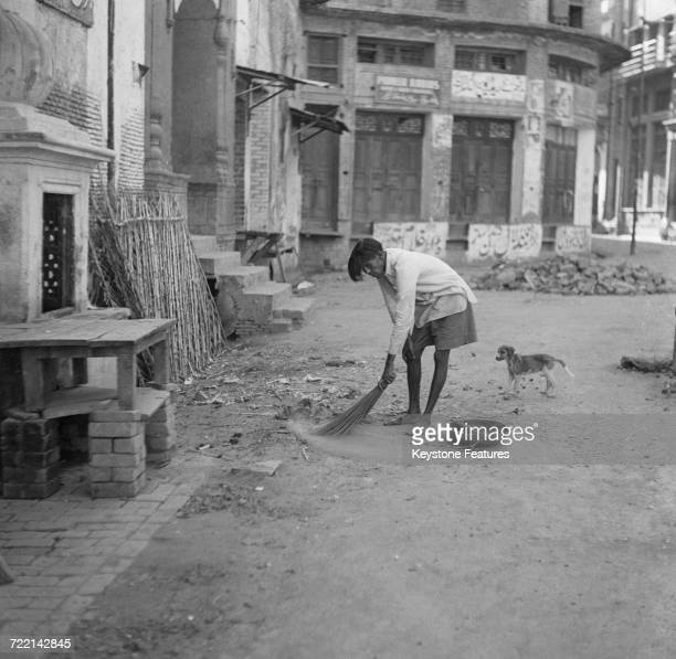 A street sweeper at work after communal riots in Amritsar Punjab during the Partition of British India March 1947 The man has permission to work but...
