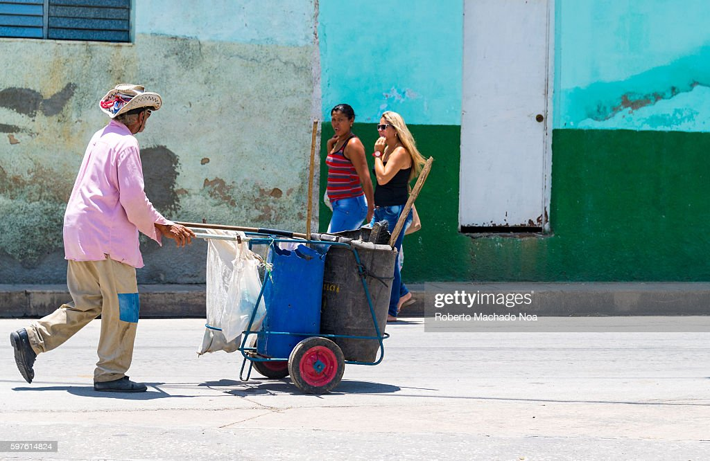 Street sweeper with cart looking at two beautiful Cuban women Cuban lifestyle or way of life