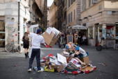 A street trader dumps discarded cardboard boxes onto a trash pile for recycling at the Campo de Fiori outdoor market in Rome Italy on Saturday July...